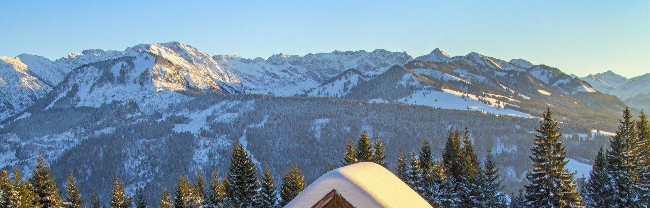 Verschneite Hütte vor Allgäuer Winterpanorama © Dominic Ultes